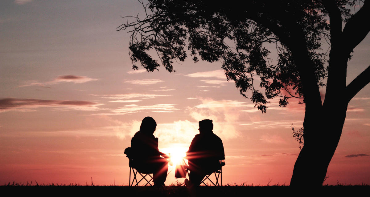 Silhouettes of two people sitting and talking